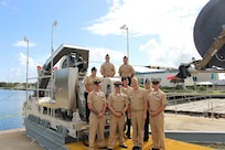Rear Adm. John Neagley, Program Executive Officer for Unmanned and Small Combatants, poses with sailors attached to USS Forth Worth (LCS 3) at a test event for the DART mission system at the Harbor Branch Oceanographic Institute in Fort Pierce, Florida.