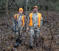 Eli and Randy Randolph don blaze orange, a crossbow, and backpack of gear as they hike to their staked-out hunting location in Carthage, Tenn., Dec. 1, 2018.  (USACE photo by Ashley Webster)
