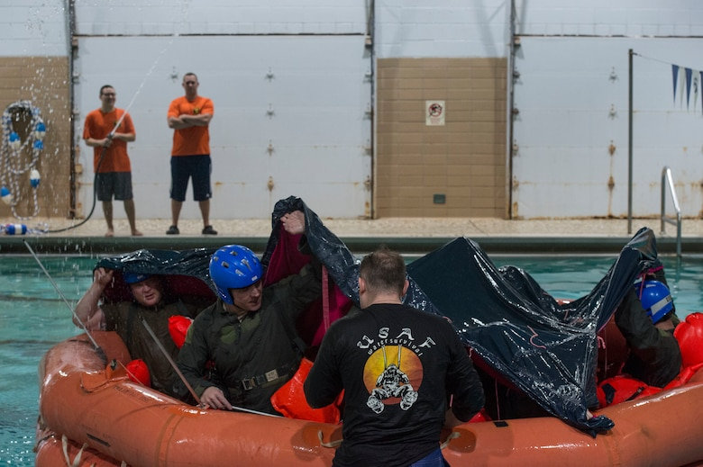 U.S. Air Force Staff Sgt. Mark Belcher, the NCO in charge of continuation training assigned to the 97th Operations Squadron, instructs members on setting up an F-2B raft canopy during a water survival refresher course,