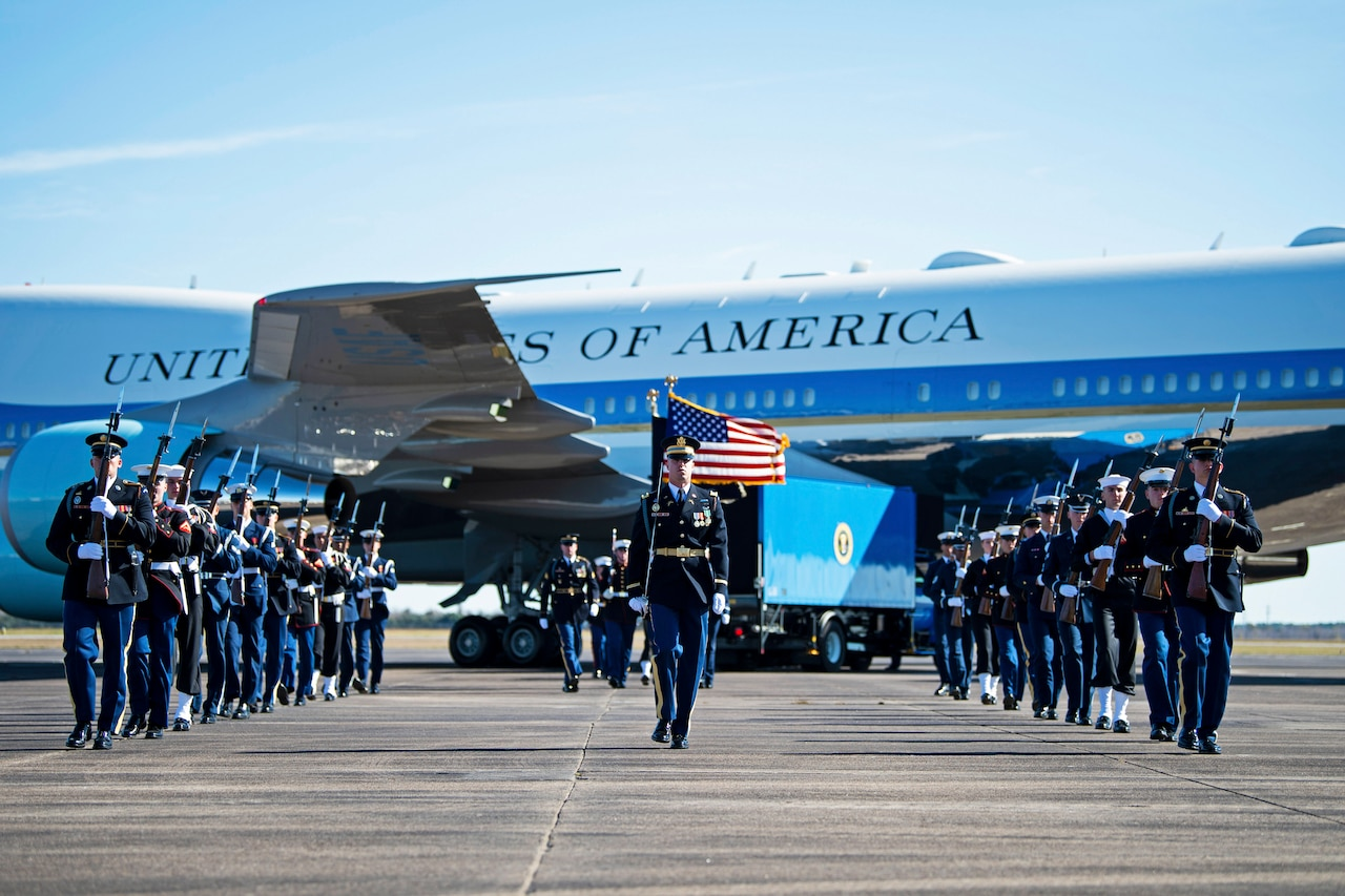 A military honor guard walks off after taking part in a departure ceremony honoring former President George H.W. Bush.