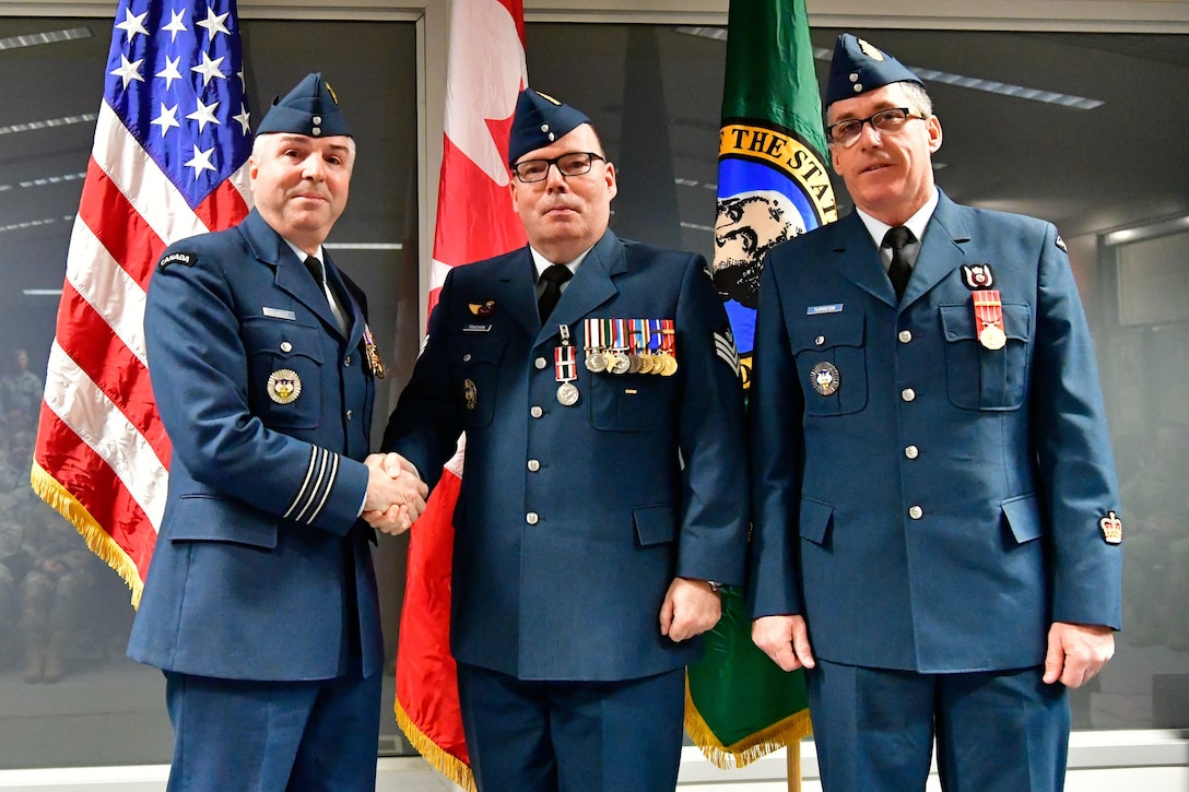 Royal Canadian Air Force Sgt. Yves Truchon (center), Western Air Defense Sector Canadian Detachment command and control battle manager, is awarded the Canadian Armed Forces Special Service Medal with NATO bar from Lt. Col. Michael Fawcett, WADS Canadian Detachment commander (left), Dec. 1, 2018 at Joint Base Lewis-McChord, Washington.  The medal was awarded for Truchon's exceptional service conducting operations as part of Task Force 2011 (409th Fighter Squadron) and Task Force 2013 (425th Fighter Squadron) during Operation Ignition, the RCAF contribution to the NATO air policing mission over Iceland, providing airborne surveillance and interception capabilities to meet Iceland's peacetime preparedness needs. The Special Service Medal was created to recognize members of the Canadian Armed Forces who have performed a service determined to be under exceptional circumstances, in a clearly defined locality for a specified duration.  The SSM is always issued with a bar that specifies the special service being recognized, each bar having its own criteria. (U.S. Air National Guard photo by Maj. Kimberly D. Burke)