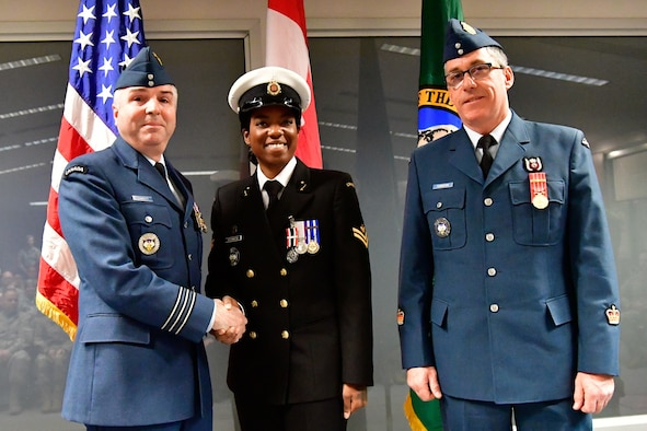 Royal Canadian Navy Master Seaman Malisa Ogunniya (center), Western Air Defense Sector Canadian Detachment chief clerk, is awarded the Canadian Armed Forces Special Service Medal with NATO bar from Lt. Col. Michael Fawcett, WADS Canadian Detachment commander (left), Dec. 1, 2018 at Joint Base Lewis-McChord, Washington.  The medal was awarded for Ogunniya's exceptional service in support of operations while onboard Her Majesty's Canadian Ship Winnipeg from July 2015 through January 2016.  HMCS Winnipeg conducted operations under the standing NATO Maritime Group Two as part of Operation Reassurance, NATO's mission to build maritime situational awareness in order to detect, deter and disrupt terrorism in the Mediterranean Sea. The Special Service Medal was created to recognize members of the Canadian Armed Forces who have performed a service determined to be under exceptional circumstances, in a clearly defined locality for a specified duration.  The SSM is always issued with a bar that specifies the special service being recognized, each bar having its own criteria. (U.S. Air National Guard photo by Maj. Kimberly D. Burke)