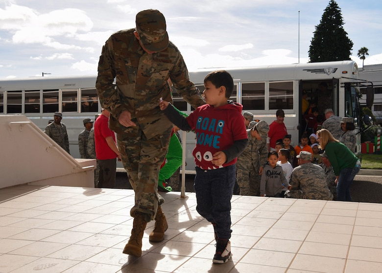 Maj. Gen. Stephen Whiting, 14th Air Force commander and Deputy Joint Force Space Component commander, walks with a child into the Pacific Coast Club during Operation Kids Christmas at Vandenberg Air Force Base, Calif. Dec. 1, 2018. Vandenberg hosts the 59th annual Operation Kids Christmas here, expecting 200 kids from nearby cities to partake in the planned games, crafts, lunch and Christmas gifts.