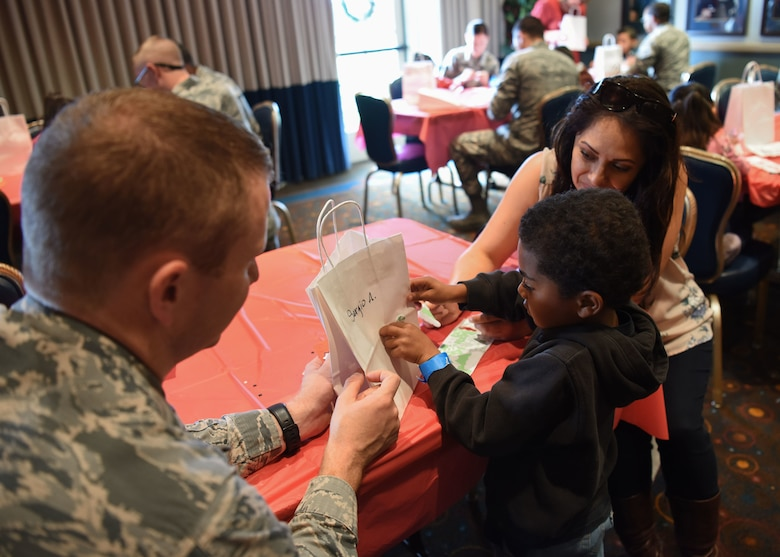 Maj. Kenneth Peters, 30th Space Wing Comptroller Squadron commander, assists his assigned child during crafts at Operation Kids Christmas at the Pacific Coast Club at Vandenberg Air Force Base, Calif. Dec. 1, 2018. Vandenberg hosts the 59th annual Operation Kids Christmas here, expecting 200 kids from nearby cities to partake in the planned games, crafts, lunch and Christmas gifts.