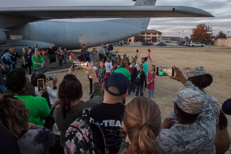 Members of the 97th Air Mobility Wing record videos of their children performing various holiday songs, Nov. 29, 2018, at Altus Air Force Base, Okla. Every year children of the 97th Air Mobility Wing perform songs for the holiday tree lighting event. (U.S. Air Force photo by Senior Airman Cody Dowell)