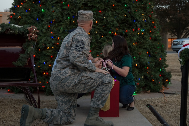 97th Air Mobility Wing leadership and Sami Chase, spouse of U.S. Air Force Senior Airman Austin Chase, an emergency management journeyman assigned to the 97th Civil Engineer Squadron, light the holiday tree as part of the annual Holiday Tree Lighting event, Nov. 29, 2018, at Altus Air Force Base, Okla. Every year during the event a deployed member's spouse joins the commander and command chief to light the holiday tree to honor all deployed members and their families. (U.S. Air Force photo by Senior Airman Cody Dowell)