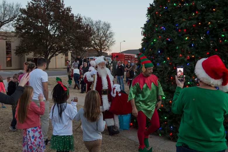 Members of the 97th Air Mobility Wing gather to greet Santa Claus, Nov. 29, 2018, at Altus Air Force Base, Okla. After the holiday tree is lit, Santa Claus greets the members of the 97th AMW after arriving in a firetruck. (U.S. Air Force photo by Senior Airman Cody Dowell)