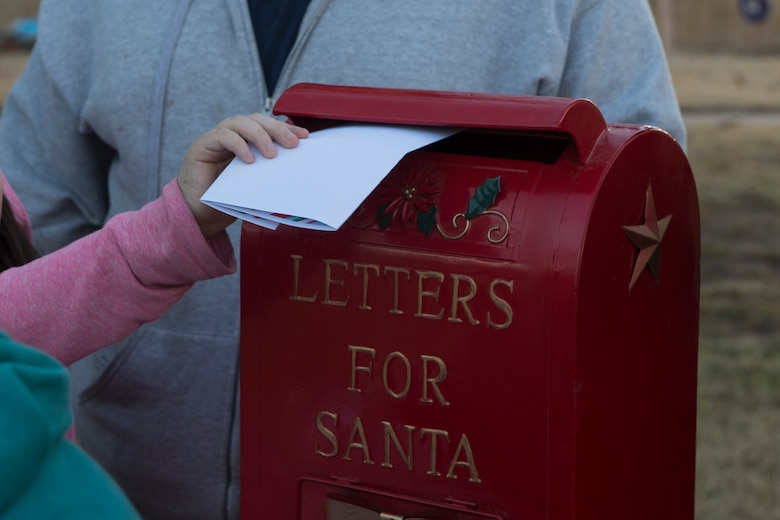 A member of the 97th Air Mobility Wing inserts a letter for Santa Claus into a mailbox during the Holiday Tree Lighting Event, Nov. 29, 2018, at Altus Air Force Base, Okla. Several different actives were set up for the Airmen of the 97th AMW and their families to celebrate the beginning of the holiday season. (U.S. Air Force photo by Senior Airman Cody Dowell)