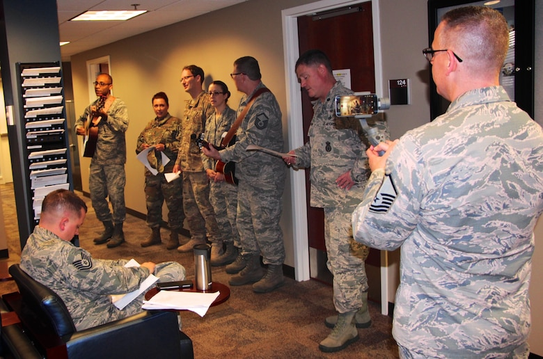 Col. Lance Turner, the 932nd Mission Support Group's multi-talented commander, along with other officers and enlisted leadership, stopped by the 932nd Force Support Squadron customer service waiting room to share in some holiday song Dec 2, 2018, at Scott Air Force Base, Illinois.  They sang various songs during the Unit Training Assembly to help Airmen pass the time in the line.  The other talented guitar player, third from the right, is Master Sgt. Tony Loving, and all the action was captured for historical documentation by Master Sgt. Christopher Parr on his tripod and video camera combo at far right.  (U.S. Air Force photo by Lt. Col. Stan Paregien)