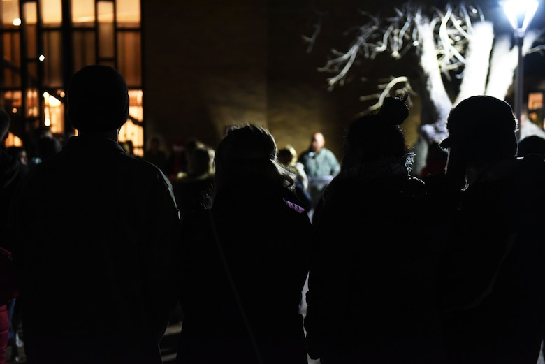 Airmen and their families listen to a speech during the tree lighting ceremony at the Freedom Chapel on Ellsworth Air Force Base, S.D., Nov. 30, 2018. Airmen and their families came out to celebrate the lighting of the base tree and to start the holidays in a festive and family-friendly environment where multiple religions were represented. (U.S. Air Force photo by Airman 1st Class Thomas Karol)