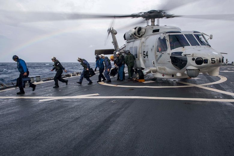 WATERS SOUTH OF JAPAN (Dec. 4, 2018) Japan Maritime Self-Defense Force (JMSDF) sailors, assigned to the JMSDF destroyer JS Hyuga (DDH-181), depart a JMSDF MH-60K Sea Hawk helicopter on the flight deck aboard the Arleigh Burke-class guided-missile destroyer USS Benfold (DDG 65). Benfold is forward-deployed to the U.S. 7th Fleet area of operations in support of security and stability in the Indo-Pacific region.