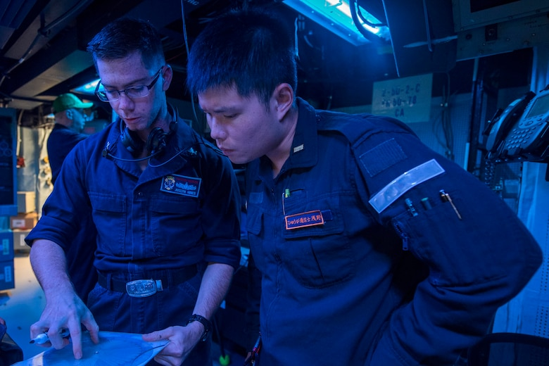 WATERS SOUTH OF JAPAN (Dec. 4, 2018) Sonar Technician (Surface) 2nd Class Joseph Hines, from Denver, explains how to use a range finder to Japan Maritime Self-Defense Force (JMSDF) Ensign Asano Shinchi, assigned to the JMSDF destroyer JS Hyuga (DDH-181), in the sonar control room aboard the Arleigh Burke-class guided-missile destroyer USS Benfold (DDG 65). Benfold is forward-deployed to the U.S. 7th Fleet area of operations in support of security and stability in the Indo-Pacific region.
