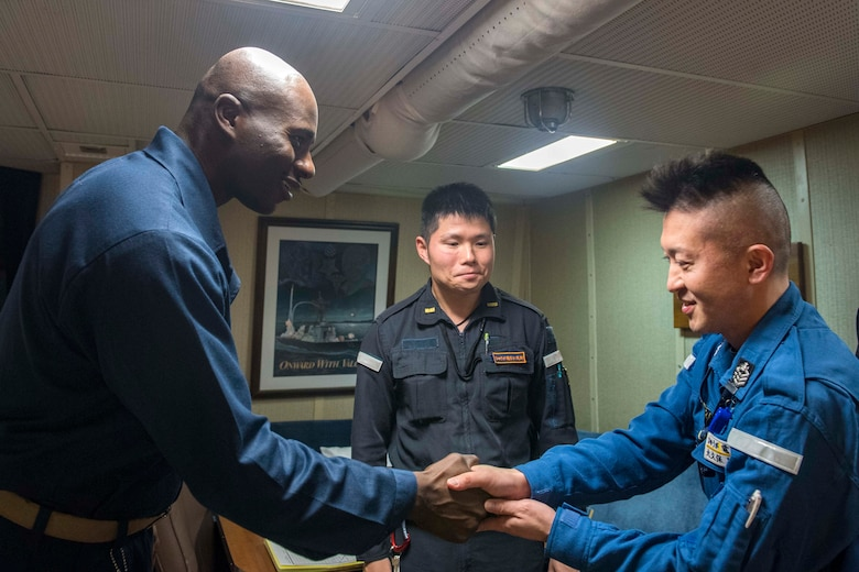 WATERS SOUTH OF JAPAN (Dec. 4, 2018) Cmdr. Leroy Mitchell, commanding officer of the Arleigh Burke-class guided-missile destroyer USS Benfold (DDG 65), greets Japan Maritime Self-Defense Force (JMSDF) Chief Operations Specialist Hideki Okubo, assigned to the JMSDF destroyer JS Hyuga (DDH-181), in the captain's cabin during a tour aboard Benfold. Benfold is forward-deployed to the U.S. 7th Fleet area of operations in support of security and stability in the Indo-Pacific region.