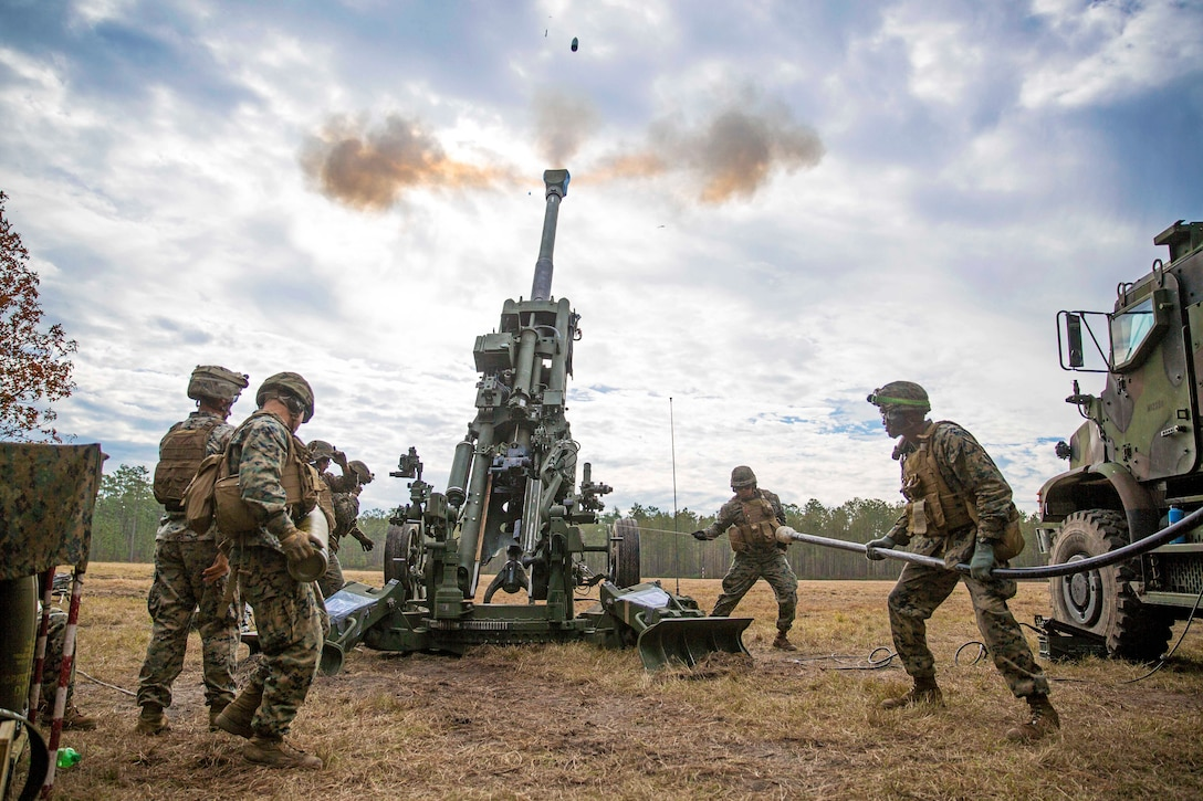 Several Marines fire an M777 howitzer.