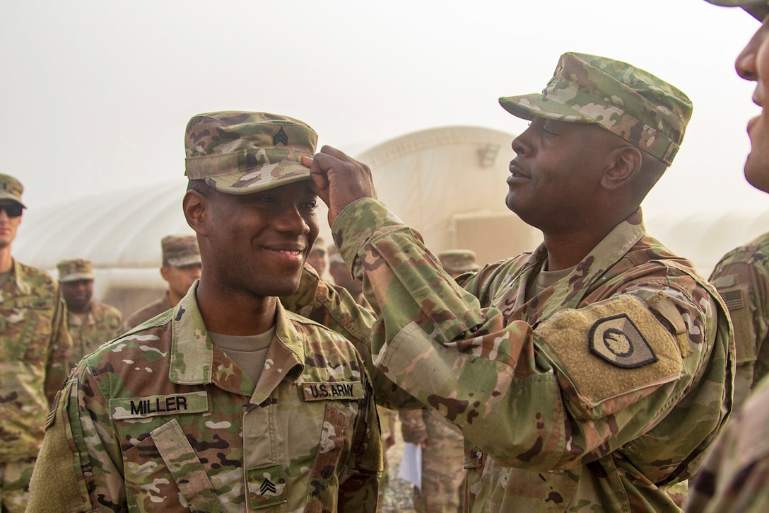 A soldier smiles as another pins his hat during a promotion ceremony.