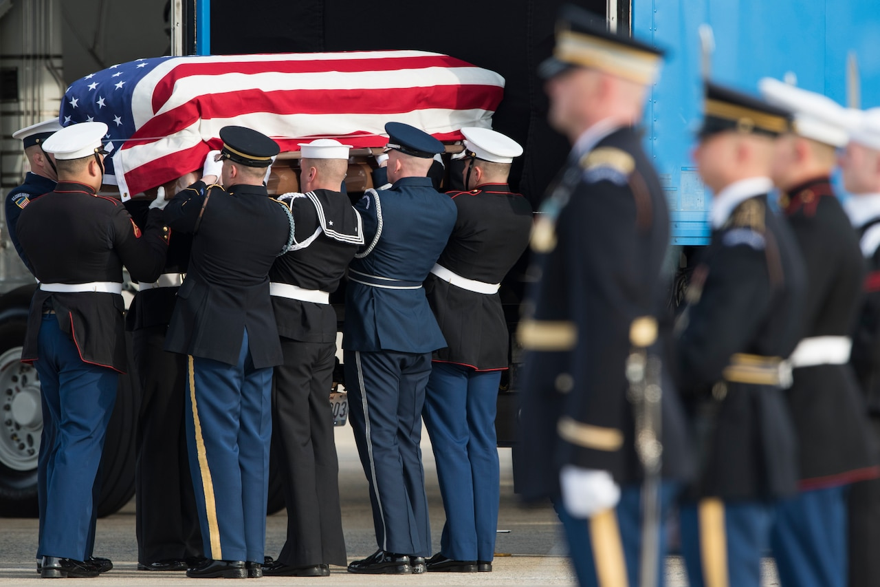 Service members lift a flag-draped coffin into a truck.