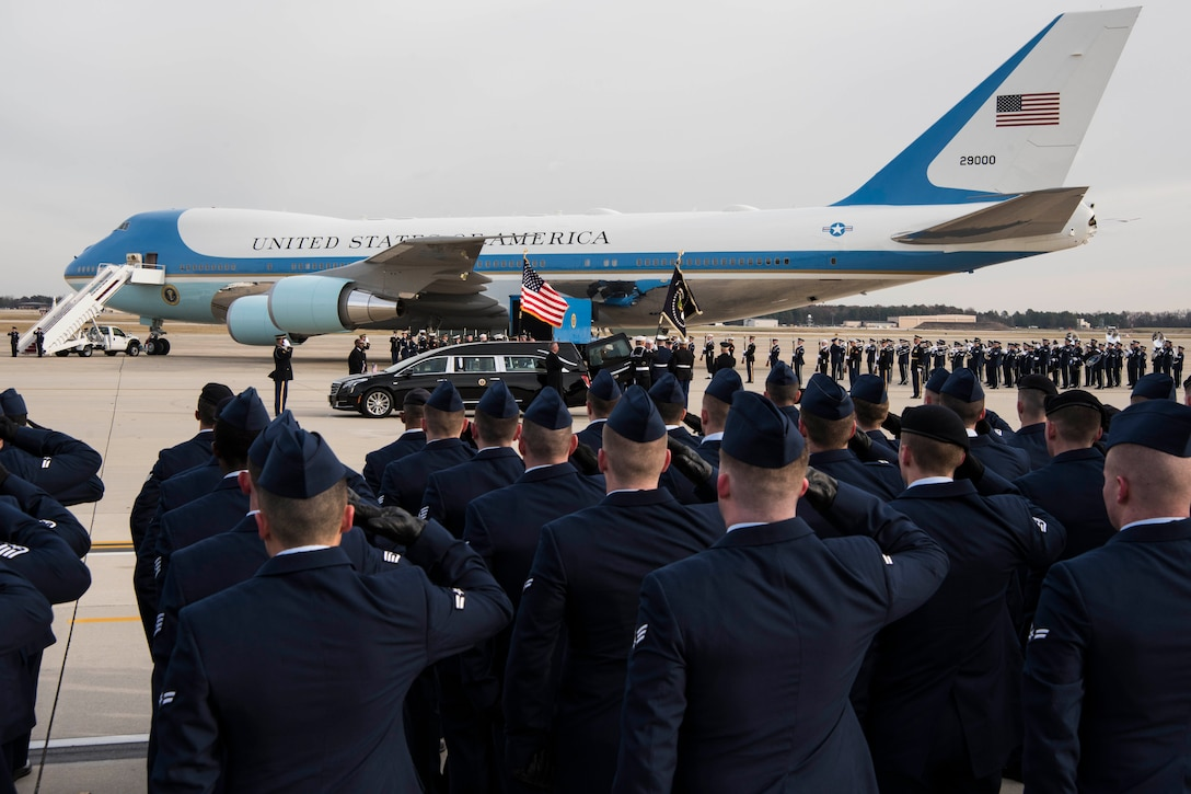 A group of service members salute as a hearse pulls alongside Air Force One.