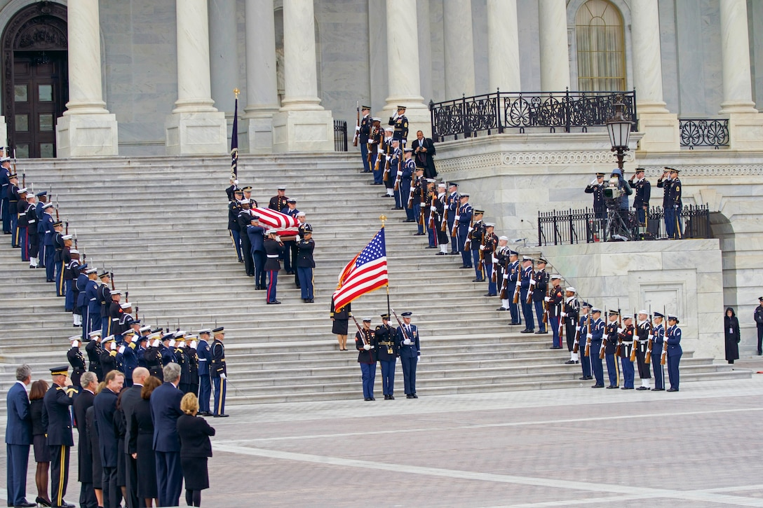 Service members bring a flag-draped coffin down the steps of the U,S, Capitol.