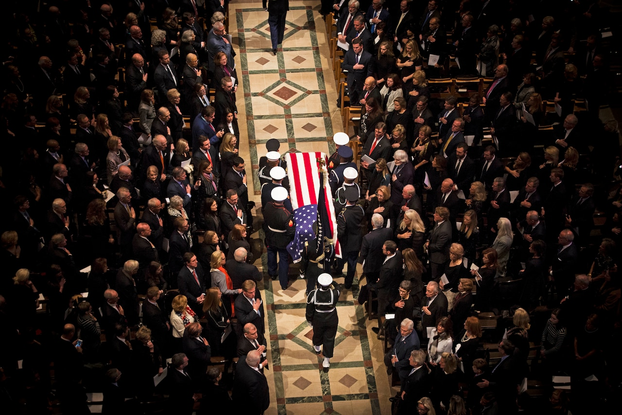 Seen from overhead,  service members carry a casket down the aisle while funeral attendees look on.