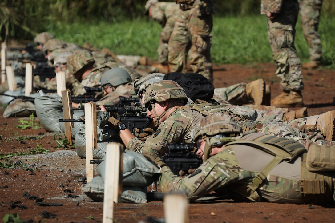 A row of soldiers aim rifles from the ground.