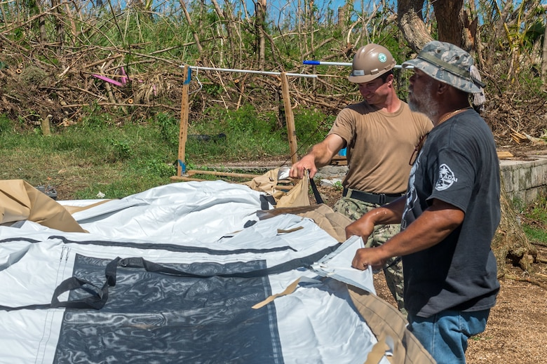 Commonwealth of the Northern Marianas Islands (Nov. 7, 2018) Builder Constructionman David Woods, assigned to Naval Mobile Construction Battalion 1, and a Tinian official erect a FEMA-provided tent for a Tinian family whose home was destroyed by Super Typhoon Yutu. Service members from Joint Region Marianas and Indo-Pacific Command are providing Department of Defense support to the Commonwealth of the Northern Mariana Islands' civil and local officials as part of the FEMA-supported Super Typhoon Yutu recovery efforts.