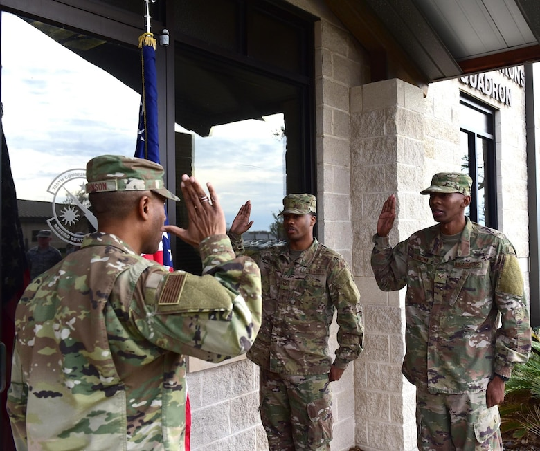 Air Force Maj. James Johnson, 325th Communication Squadron commander, gives the oath of enlistment to Staff Sgt. Abrahm Paulding (center) and Senior Airman Antoine Brown (right), 325th CS cyber systems supervisors, during their re-enlistment ceremony at Tyndall Air Force Base, Fla., Nov. 30, 2018. The ceremony was the first to take place on Tyndall since Hurricane Michael hit in October. (U.S. Air Force photo by Senior Airman Cody R. Miller)