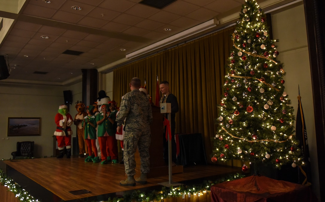 Airmen dressed as holiday characters join U.S. Air Force Col. Britt Hurst on stage during a holiday tree lighting ceremony.