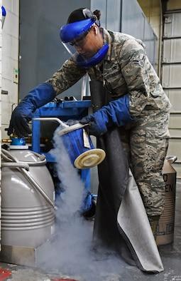 U.S. Air Force Airman 1st Class Sondra Saul, 20th Equipment Maintenance Squadron aircraft metals technician apprentice, fills a bucket with liquid nitrogen in the metal shop at Shaw Air Force Base, S.C., Nov. 30, 2018.