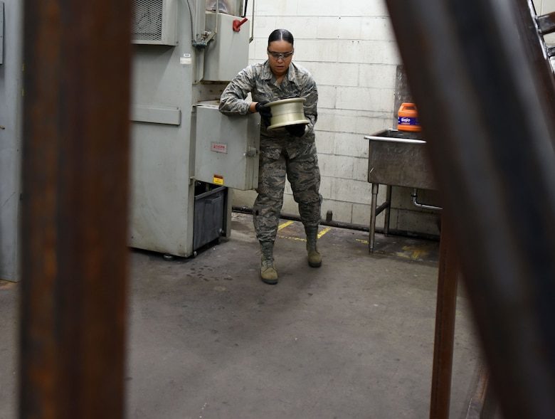 U.S. Air Force Airman 1st Class Sondra Saul, 20th Equipment Maintenance Squadron aircraft metals technician apprentice, retrieves an F-16 Fighting Falcon wheel bearing, from an oven in the metal shop, at Shaw Air Force Base S.C., Nov. 30, 2018.