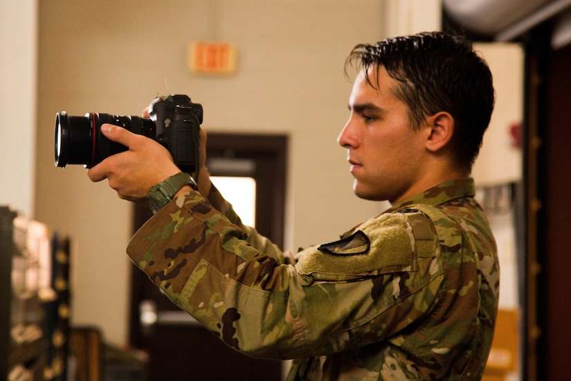 A soldier checks a camera.