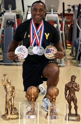 Army Capt. Johnny Dotson, displaying his award from the 2018 Drug Free Athletic Coalition World Championships, along with other medals he has won in bodybuilding competitions.