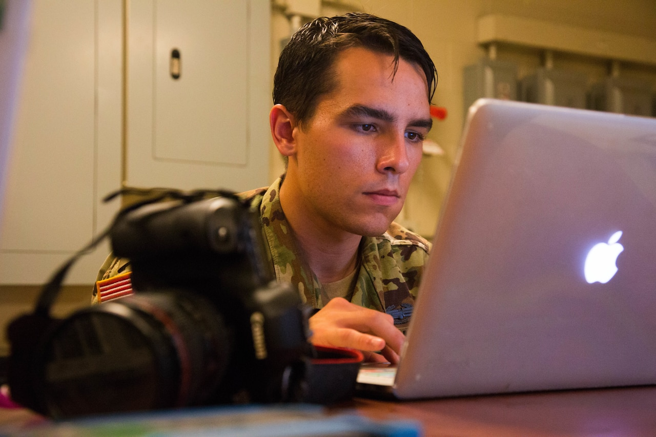 Army Spc. Austin Boucher looks at a computer.
