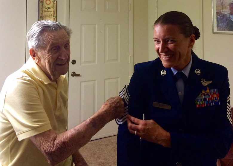 U.S. Air Force Lt. Col. (retired) Joseph S. Pesek, tacks chief master sergeant stripes onto his grandaughter Chief Master Sgt. Amanda J. Stift in 2015. Stift is the 403rd Wing command chief master sergeant and shares her grandfather's account of Dec. 7, 1941. Pesek is a World War II veteran who served in the U.S. Army Air Forces and U.S. Air Force. He was a technical sergeant stationed at Hickam Field, Hawaii, during the attack on Pearl Harbor. (Courtesy photo)