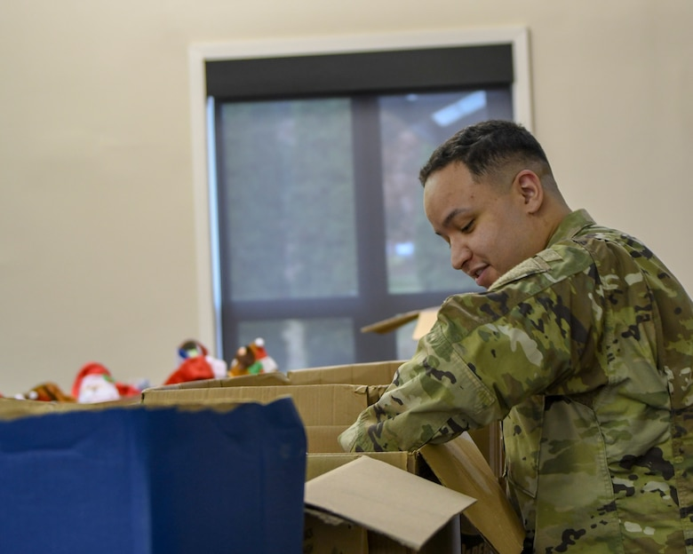 Staff Sgt. Brandon Simmons, a personnel helper with the 910th Mission Support Group, looks through boxes of donated toys for his two daughters in the Kubli Morale and Wellness Center at Youngstown Air Reserve Station, Dec. 1, 2018.