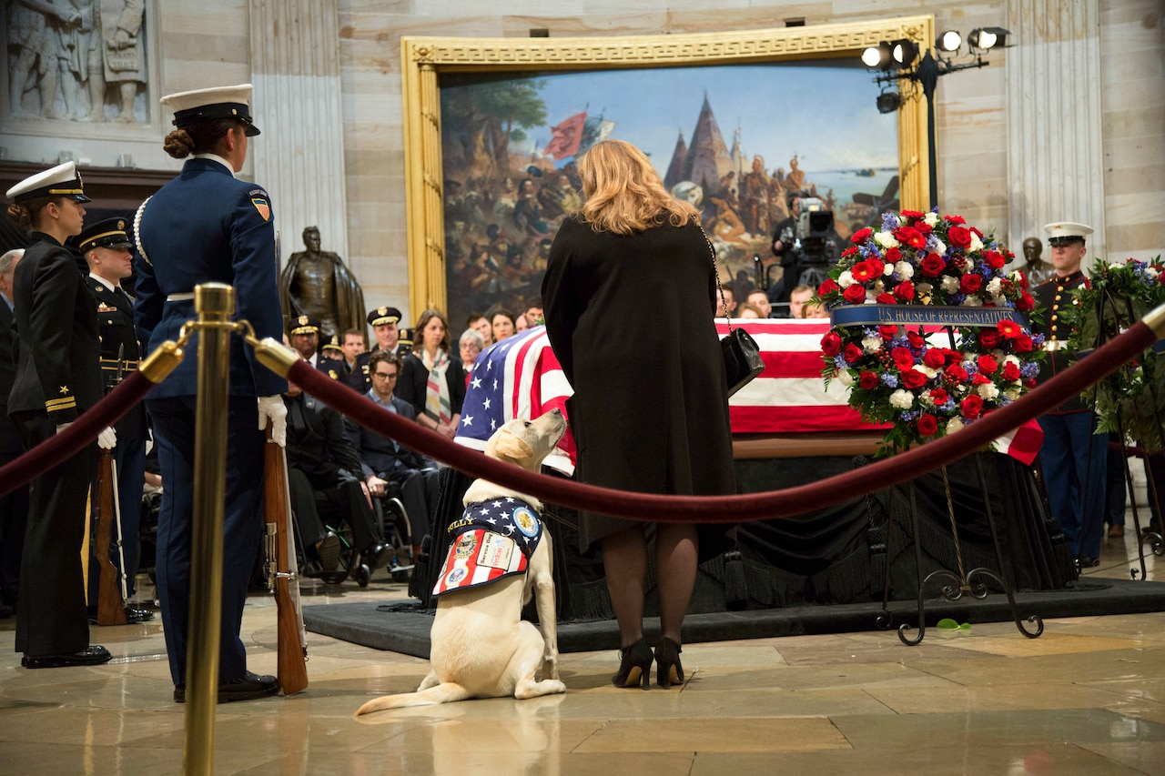 Service members, a woman and a service dog stand beside George H.W. Bush's casket at a funeral service