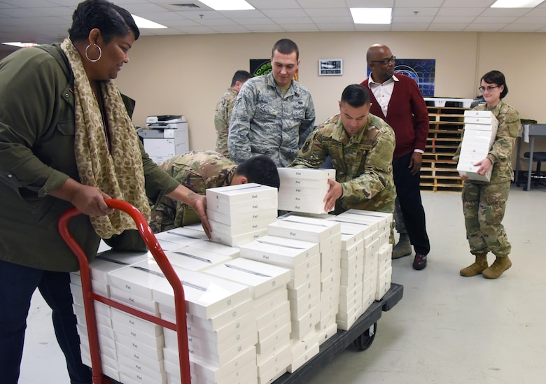 Members of the 81st Communications Squadron load 200 iPads at Keesler Air Force Base, Miss., Dec. 6, 2018. The 81st CS joined efforts with its honorary commander, Jade Ferguson, Mississippi Public Service Commission, Southern District district director, in identifying a school in need. Through this community partnership 200 iPads, valued at $72,000, were donated to the pre-kindergarten through second grade school for the opportunity of exploring science, technology, engineering, and mathematics (STEM). (U.S. Air Force photo by Kemberly Groue)