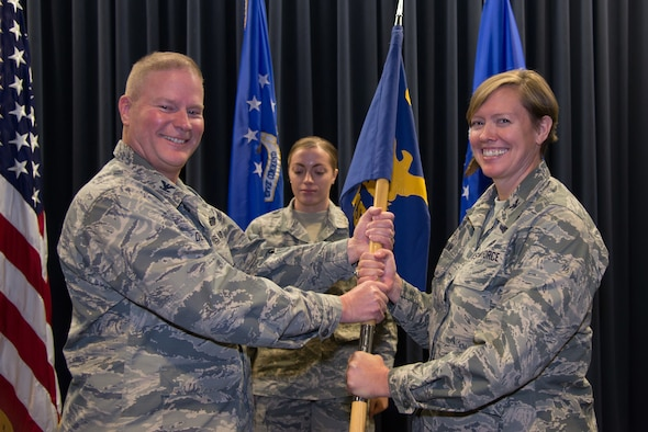 Col. James DeVere, the 302nd Airlift Wing commander, passes the 302nd Mission Support Group guidon to Col. Tara Nolan, the new 302nd MSG commander, during an assumption of command ceremony at Peterson Air Force Base, Dec. 1, 2018.