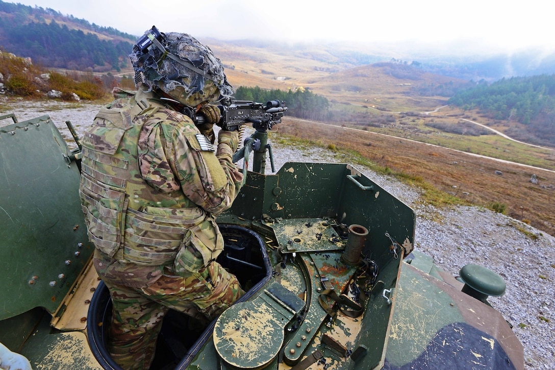 An Army paratrooper engages targets with a machine gun.