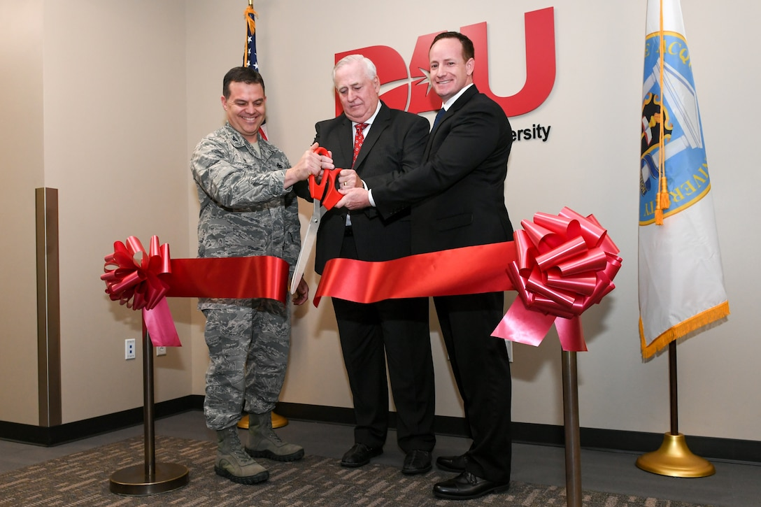 Defense Acquisition University held a grand opening ceremony Dec. 4, 2018, at its new location in the Falcon Hill complex at Hill Air Force Base, Utah. Cutting the ribbon are Col. Gabriel Lopez, 75th Mission Support Group commander, Kevin Carman, DAU West Region dean, and Jude Gronenthal, DAU West Region director. The new location will nearly double student capacity to 126 with four classrooms from its previous location. DAU is a corporate university of the Department of Defense offering acquisition, technology, and logistics training to military and federal civilians. (U.S. Air Force photo by Cynthia Griggs)