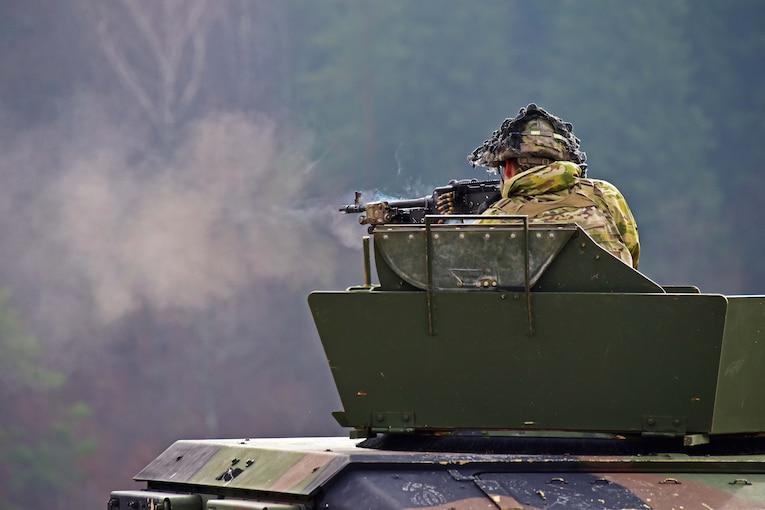 A soldier fires a machine gun from a tank.