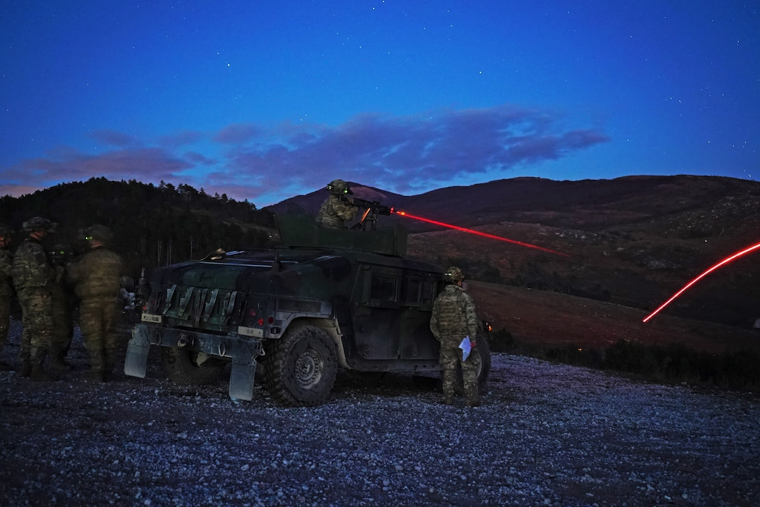 Soldiers use a machine gun mounted on a tank to fire at targets at night.