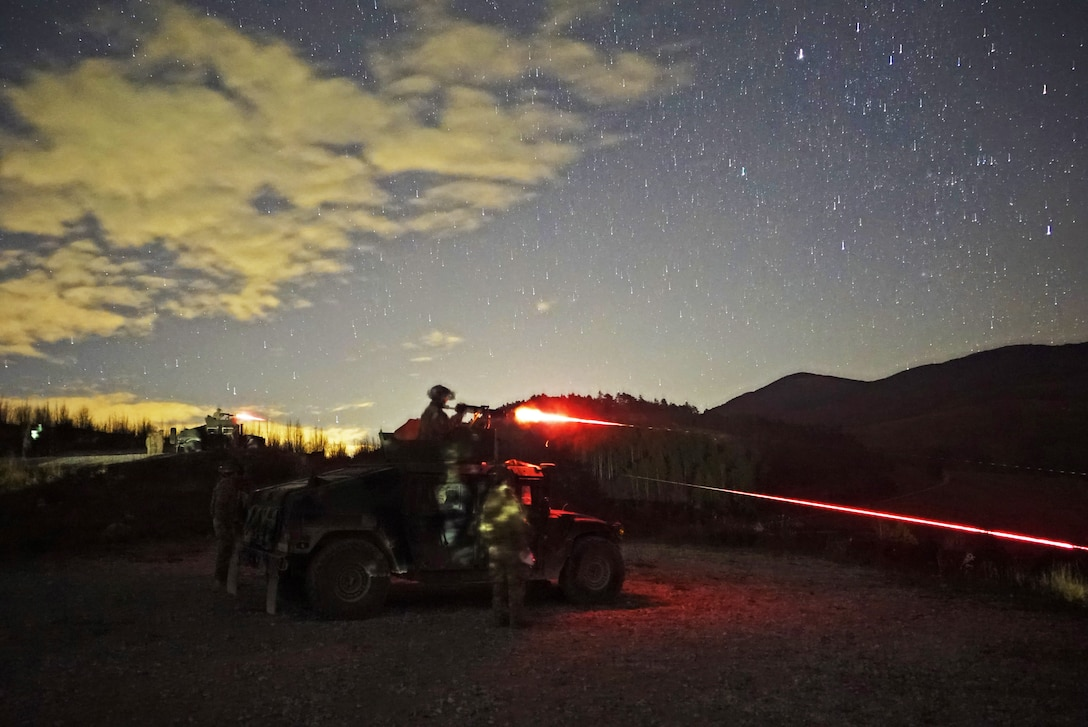 Soldiers engage targets at night with a machine gun mounted on a tank.