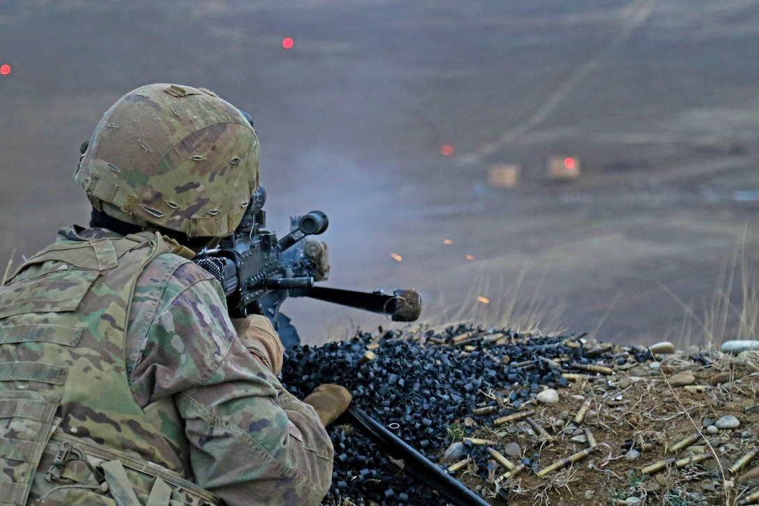 A soldier fires a machine gun from a position on a hill.