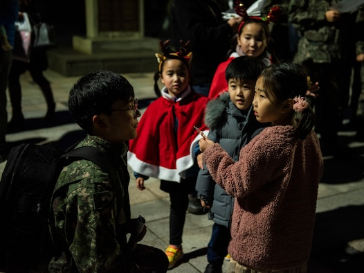 A member of the 38th Fighter Group, Republic of Korea Air Force, gives a candy cane to a child at a tree lighting ceremony at Kunsan Air Base, Republic of Korea, Nov. 29, 2018. Kunsan celebrated the start of the holiday season with a base-wide event held by the 8th FW chapel. (U.S. Air Force photo by Senior Airman Stefan Alvarez)