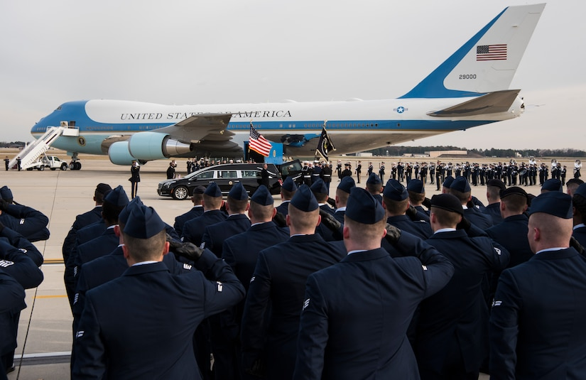 Dozens of airmen in caps and dress uniforms salute in the direction of Air Force One, which is parked on tarmac, while a casket is unloaded from a hearse. To the side and far away, the Air Force Band awaits.