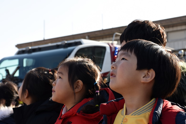 Kwon Na, Korean Christian International School student, watches as a fire truck sprays water into the air at Kunsan Air Base, Republic of Korea, Nov. 30, 2018. The students visited the 8th Civil Engineer Squadron to tour the fire station and learn more about being a firefighter. (U.S. Air Force photo by Staff Sgt. Joshua Edwards)