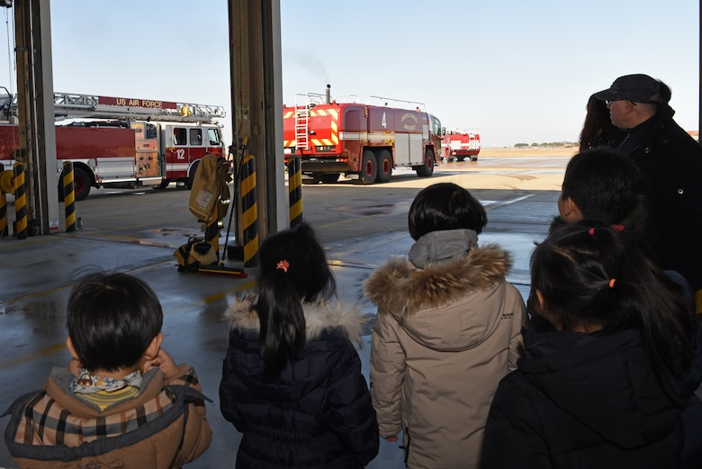 Korean Christian International School students and teachers watch 8th Civil Engineer Squadron firefighters respond to a call at Kunsan Air Base, Republic of Korea, Nov. 30, 2018. The firefighters reacted when called to assist an F-16 Fighting Falcon that needed emergency repairs. (U.S. Air Force photo by Staff Sgt. Joshua Edwards)