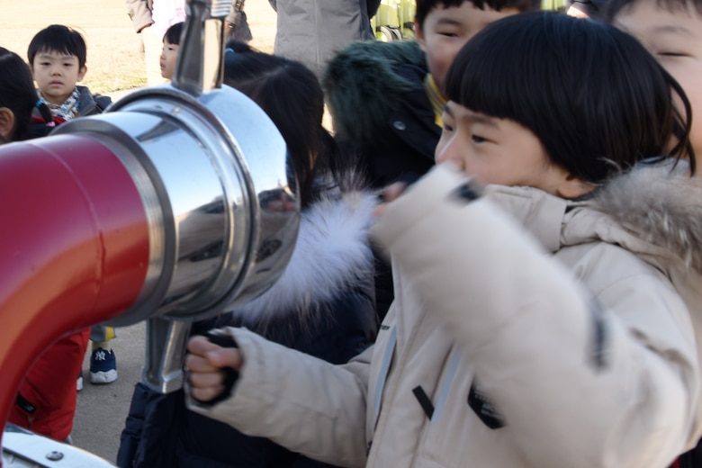Jin-yong Jeong, Korean Christian International School student, looks at a fire truck's front end hose connection during a tour of the 8th Civil Engineer Squadron fire house at Kunsan Air Base, Republic of Korea, Nov. 30, 2018. During the tour, students explored four different types of trucks the firefighters use when responding to emergencies. (U.S. Air Force photo by Staff Sgt. Joshua Edwards)