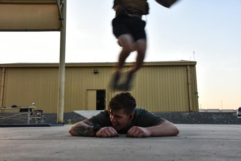 A U.S. Air Force Airman does a burpee over his partner during the EOD 134 Memorial Workout at Al Dhafra Air Base, United Arab Emirates, Nov. 30, 2018. 380th Air Expeditionary Wing Airmen, along with coalition partners, participated in the workout to honor the 134 EOD technicians from the U.S. Air Force, Army, Navy and Marine Corps that have been killed since Sept. 11, 2001. (U.S. Air Force photo by Senior Airman Mya M. Crosby)