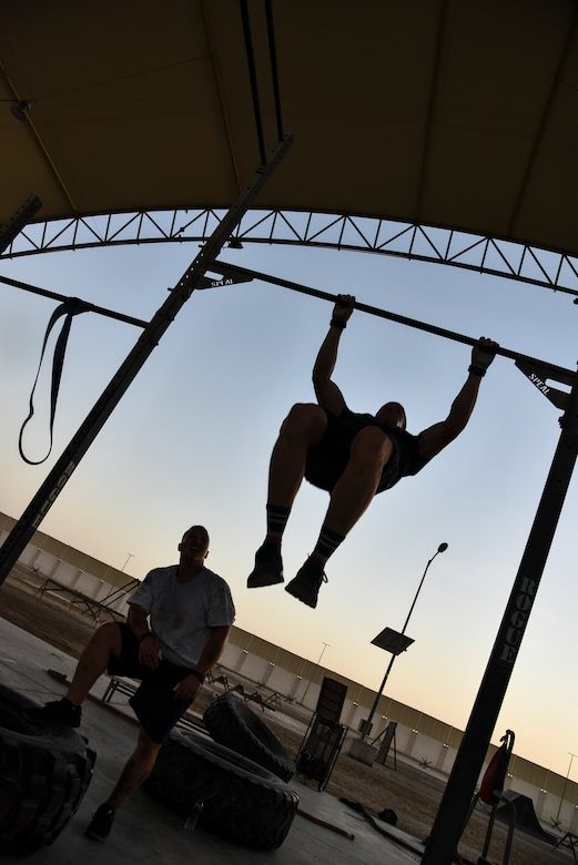 A U.S. Air Force Airman executes chest-to-bar pull-ups during the EOD 134 Memorial Workout at Al Dhafra Air Base, United Arab Emirates, Nov. 30, 2018. 380th Air Expeditionary Wing Airmen, along with coalition partners, participated in the workout to honor the 134 EOD technicians from the U.S. Air Force, Army, Navy and Marine Corps that have been killed since Sept. 11, 2001. (U.S. Air Force photo by Senior Airman Mya M. Crosby)